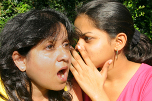 Photo of a woman whispering to another woman