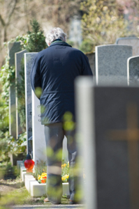 Photo of a man grieving at a grave